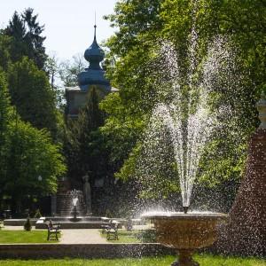 Park na pierwszym planie fontanna, w tle zabytkowy budynek