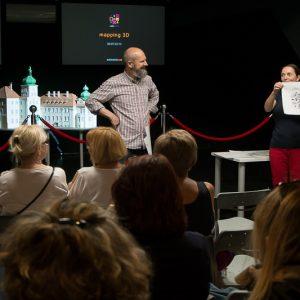 Spotkanie w sali multimedialnej, mężczyzna i kobieta prezentują rysunek na scenie