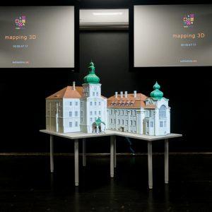Makieta pałacu nastole, w tle dwa kolorowe monitory